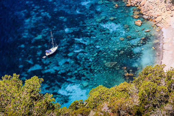 Top view of amazing blue water lagoon and anchored sailboat Beautiful scene of pristine crystal clear blue water lagoon at the coastline near the Island of Ibiza, Spain. High vista point view towards the bay with anchored sailboat, rocky sea bed and desert vegetation. Shot on Canon EOS, 85mm, ISO 100, f5.6. ibiza island stock pictures, royalty-free photos & images