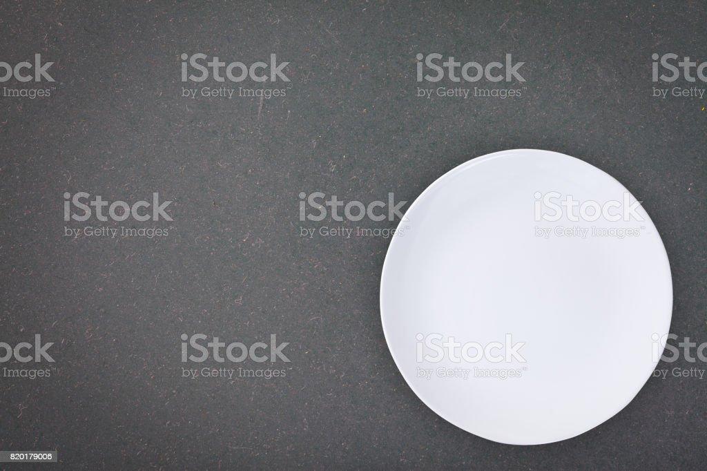 Draufsicht auf einen leeren weißen Teller platziert auf einer Tafel mit Textfreiraum. – Foto