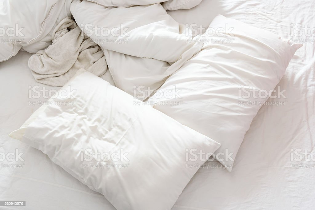 Top view of an unmade bed in a bedroom. stock photo