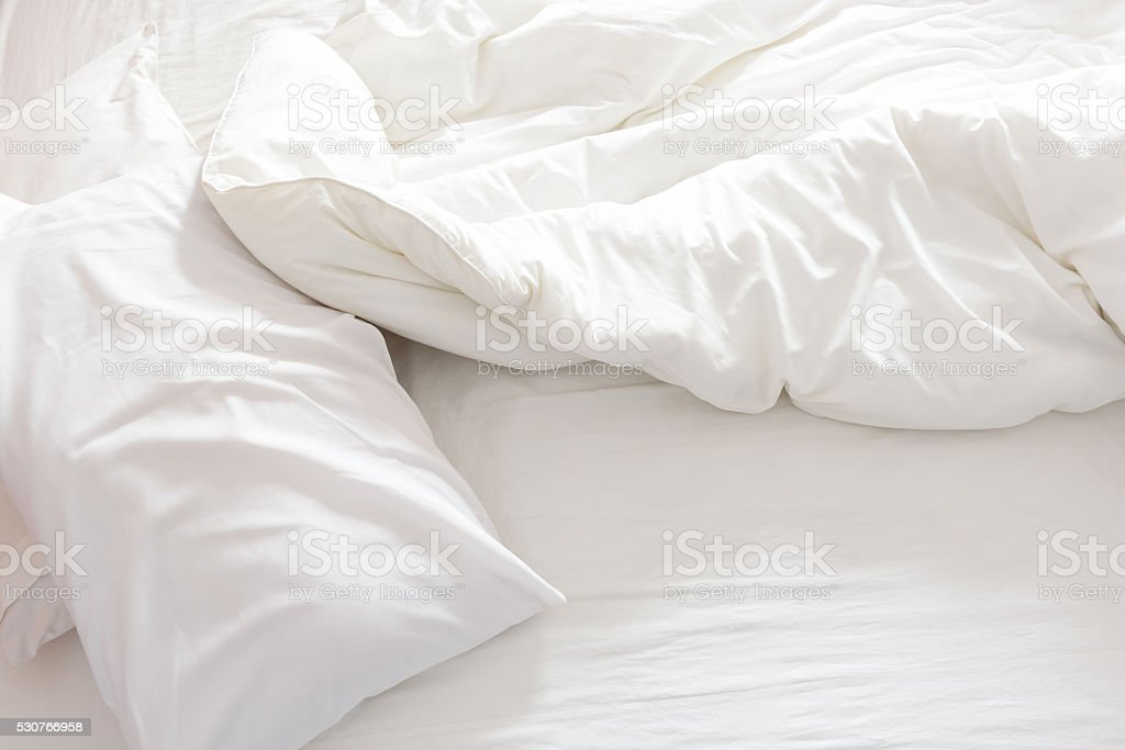 Top view of an unmade bed with crumpled bed sheet. stock photo