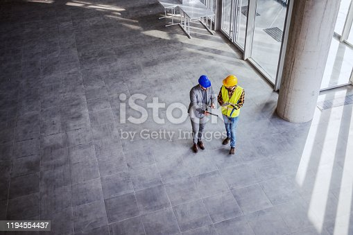 Top view of architect holding tablet and talking with construction worker about new ideas on project they working on. Building in construction process interior.