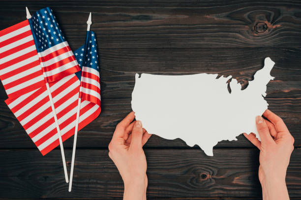 top view of arranged american flags and female hands with piece of blank map on wooden tabletop, presidents day concept stock photo