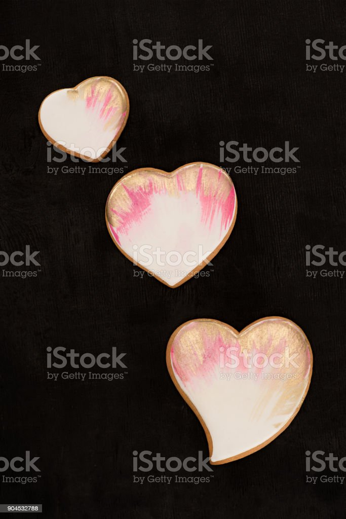 top view of arranged heart shaped cookies on dark surface stock photo