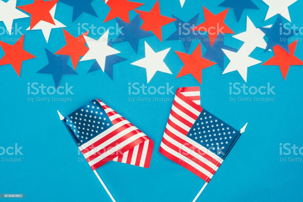 top view of arranged stars and american flags isolated on blue, presidents day celebration concept stock photo