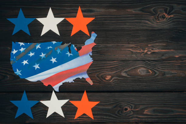 top view of arranged stars and piece of map with american flag on wooden tabletop, presidents day concept stock photo