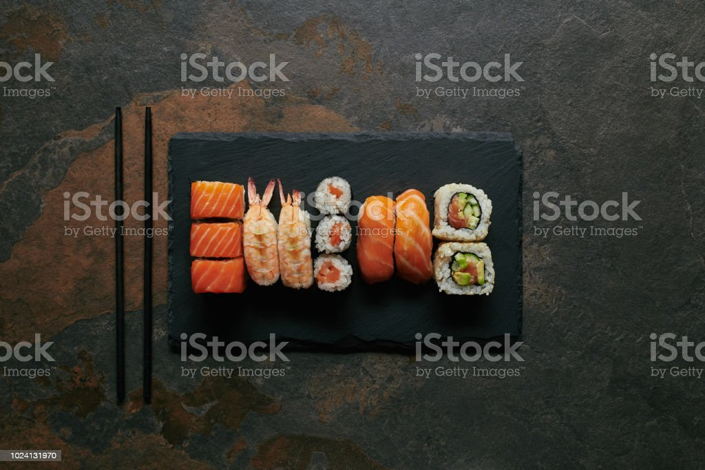 top view of arranged sushi set on black slate plate and chopsticks on...