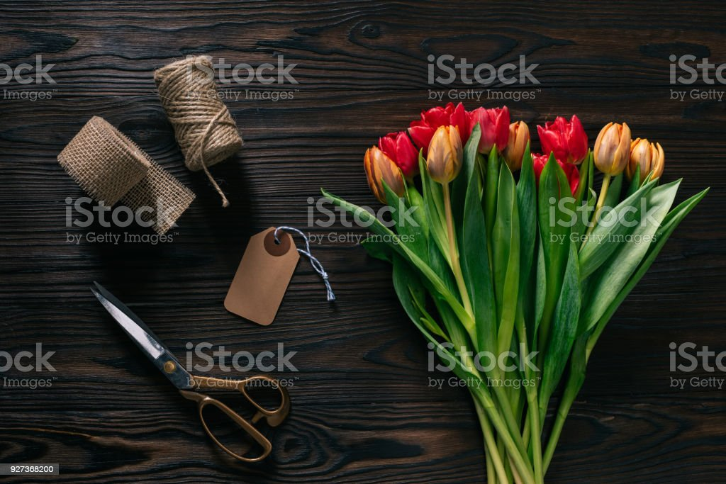 top view of arranged tulips, rope, scissors and ribbon for decoration on wooden surface - Royalty-free Arrangement Stock Photo