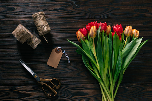 Top View Of Arranged Tulips Rope Scissors And Ribbon For Decoration On Wooden Surface Stock Photo - Download Image Now