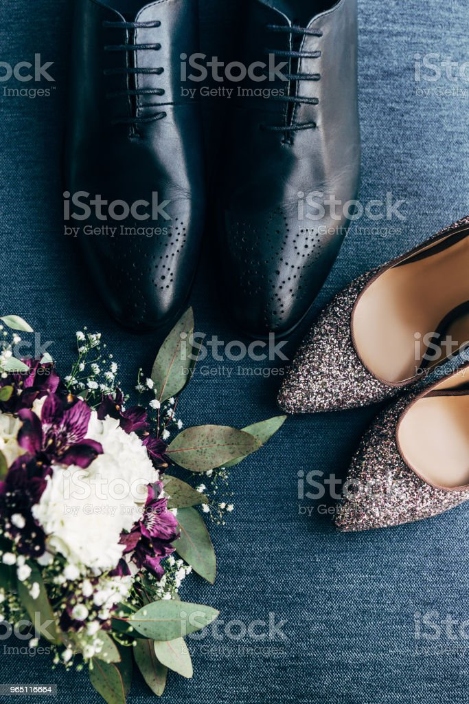 top view of arranged wedding bouquet, bridal and grooms shoes on blue background royalty-free stock photo