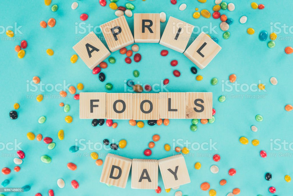 top view of arranged wooden cubes in april fools day lettering on blue surface with candies, 1 april holiday concept stock photo
