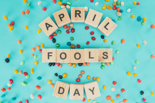 top view of arranged wooden cubes in april fools day lettering on blue surface with candies, 1 april holiday concept - april fools stock pictures, royalty-free photos & images