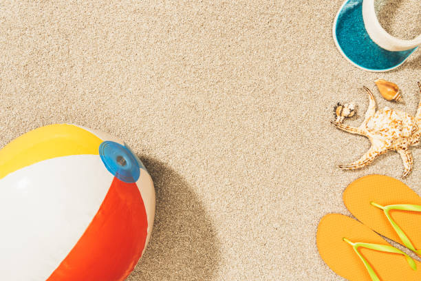 top view of arrangement of colorful beach ball, flip flops and cap on sand - beach ball stock photos and pictures