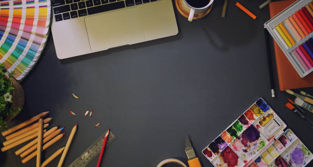Top view of artist creative studio Top view of artist creative studio with paintings tools, stationery and laptop in dark background illustrator stock pictures, royalty-free photos & images