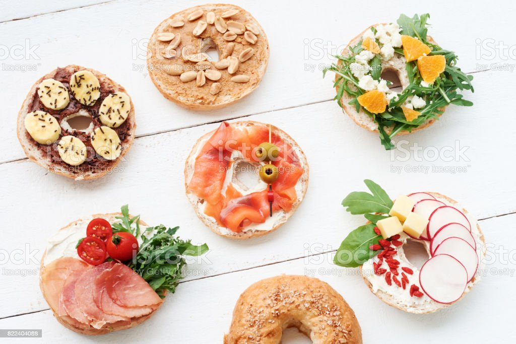 Top view of assorted bagels on white table. stock photo