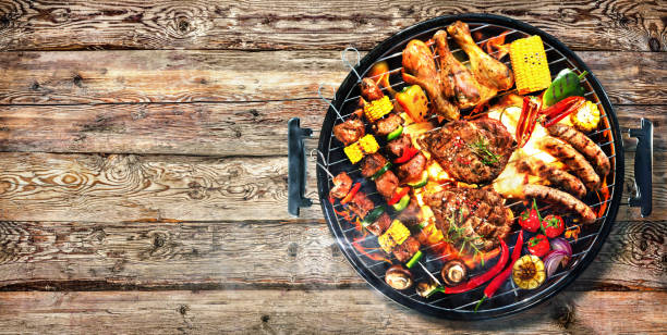 Top view of assorted delicious grilled meat with vegetables on barbecue on rustic wooden planks stock photo