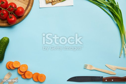 top view of assorted fresh vegetables, cookies and cutlery isolated on blue