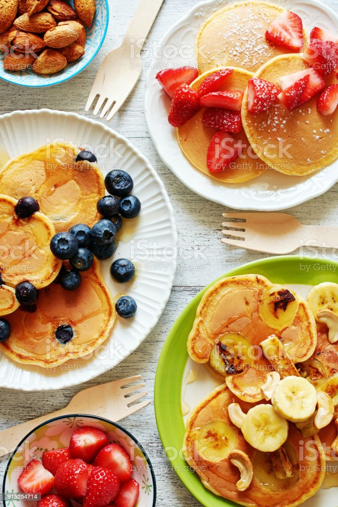Draufsicht der sortierten Pfannkuchen mit Erdbeere, Heidelbeere, Banane, Honig und Nüssen. – Foto