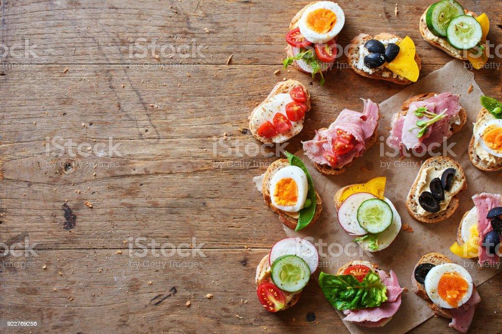 Draufsicht auf verschiedene Sandwiches mit Baguette-Brot, Käse, Schinken, Eiern, Hummus und Gemüse. – Foto