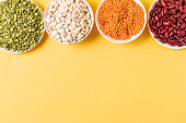 Top view of assortment of peas, lentils, beans and legumes over yellow background, with copy space.