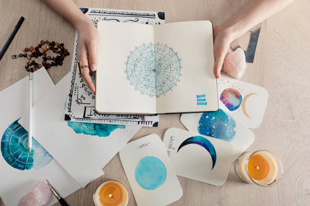 top view of astrologer holding notebook with watercolor drawings and zodiac signs on cards on table - astrologia imagens e fotografias de stock