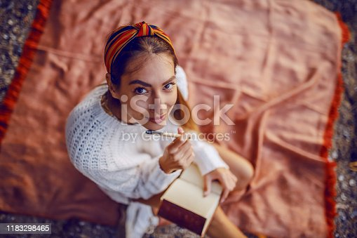 Top view of attractive caucasian brunette in sweater and with headband sitting on blanket outdoors and holding pen and diary in hands while looking at camera.
