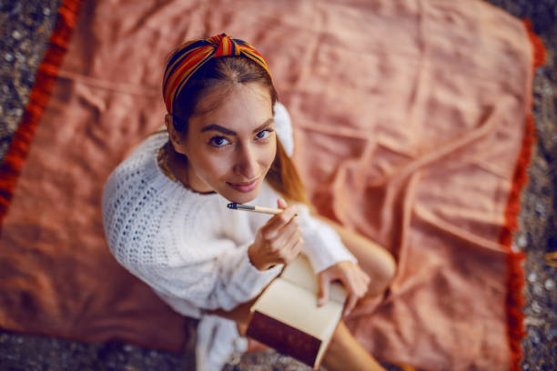 top view of attractive caucasian brunette in sweater and with headband sitting on blanket outdoors and holding pen and diary in hands while looking at camera. - writing ideas imagens e fotografias de stock