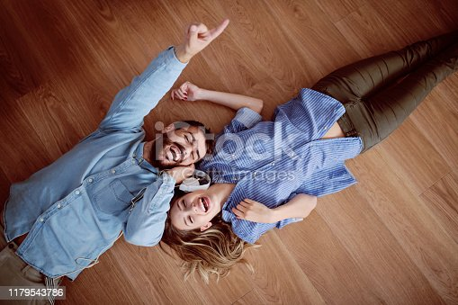Top view of attractive caucasian couple lying on the floor, listening music over the headphones and singing.