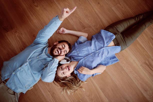 迷人的白種人夫婦躺在地板上,在耳機上聽音樂和唱歌。 - music 個照片及圖片檔