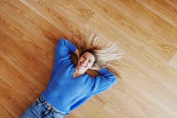 Top view of attractive charming smiling caucasian blond young woman in sweater lying on parquet and looking at camera. Top view of attractive charming smiling caucasian blond young woman in sweater lying on parquet and looking at camera. lying on back stock pictures, royalty-free photos & images