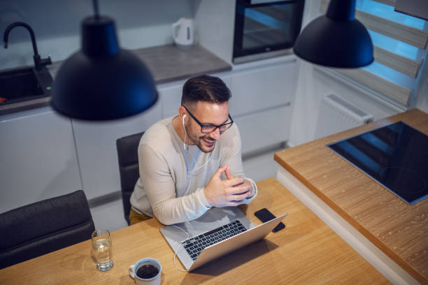 top view of attractive smiling caucasian man sitting at dining table in kitchen and having video call with his girlfriend. on table are laptop, glass with water and mug with coffee. - kitchen situations foto e immagini stock