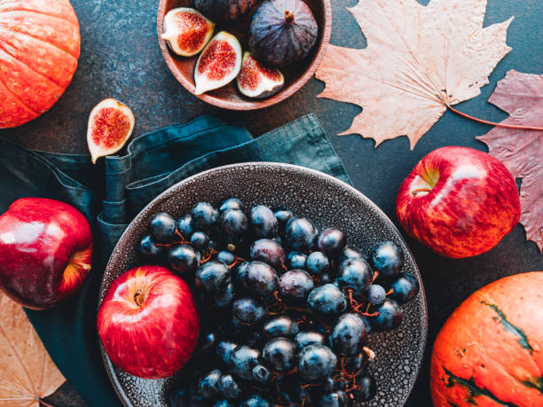 top view of autumn food flat lay with season fruits and vegetables like bangalore blue grape, red apples, pumpkins and figs on a table. - foodie stock photos and pictures