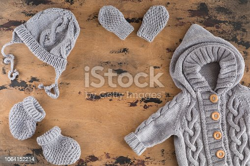 Top view of Autumn or winter baby outfit knitted clothes. Flat lay of fashion trendy look for newborn baby and accessories for the fall or winter.