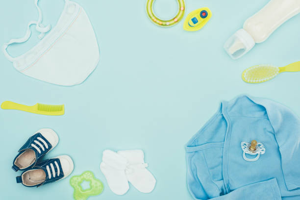 top view of baby clothes and equipment isolated on blue stock photo