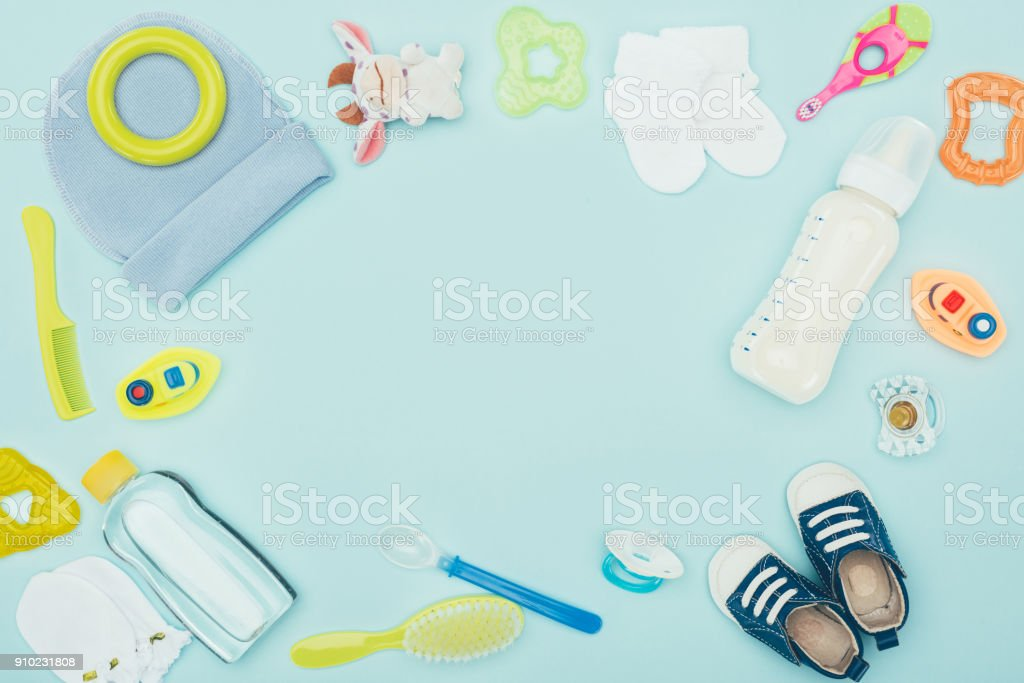 top view of baby clothes, equipment and milk isolated on blue stock photo