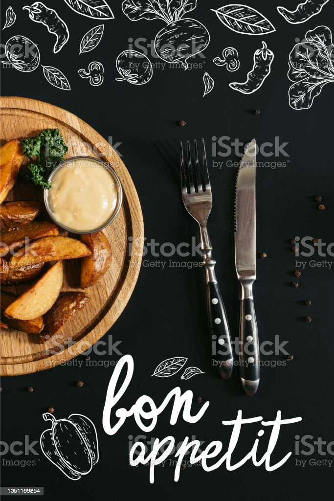 top view of baked potatoes with sauce on wooden board and fork with knife on black with 'bon appetit' lettering stock photo