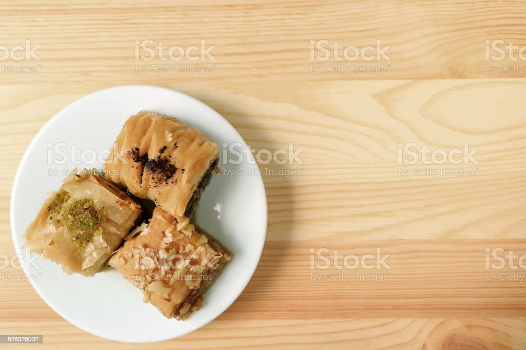 Top View of Baklava pastries on white plate served on wooden table, with free space for design and text stock photo
