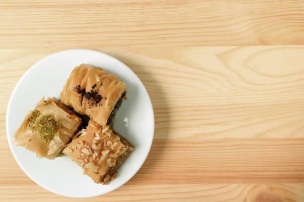Haut de la page Avis de Baklava pâtisseries sur plaque blanche servi sur table en bois, avec un espace libre pour la conception et du texte - Photo