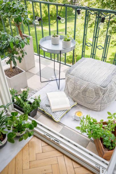 draufsicht der balkon mit licht, frischpflanzen, becher mit tee, offenes buch und material hocker in echtes foto - stockwerke des waldes stock-fotos und bilder