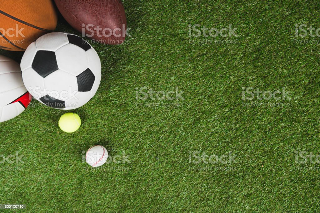 top view of balls for soccer, basketball, tennis, baseball and american football on grass pitch - foto stock