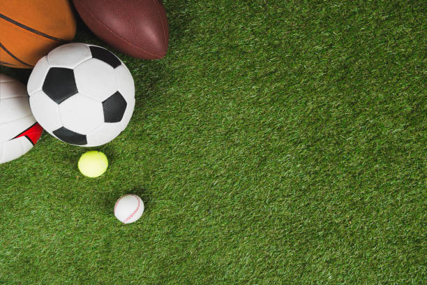 top view of balls for soccer, basketball, tennis, baseball and american football on grass pitch stock photo