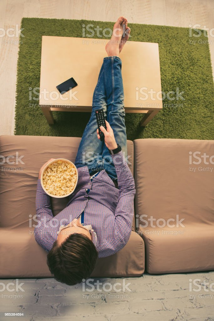 Top view of barefoot man watching tv with popcorn royalty-free stock photo