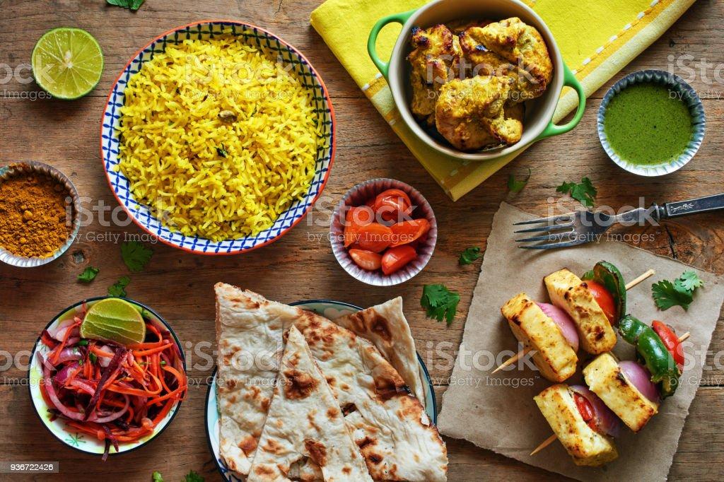 Draufsicht der Basmati-Reis, Naan-Brot, gegrillter Käse, Chicken Kebab und eingelegtes Gemüse. – Foto
