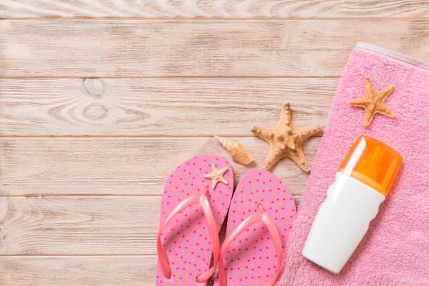 bovenaanzicht van beach flat lay accessoires. zonnebrandmiddel fles met schelpen, zeesterren, handdoek en flip-flop op houten plank achtergrond met kopieerruimte - pink and orange seashell background stockfoto's en -beelden