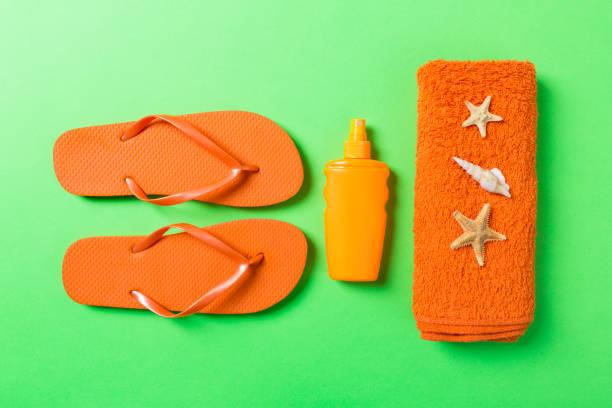 Bovenaanzicht van Beach flat lay accessoires. zonnebrandmiddel fles met schelpen, zeesterren, handdoek en flip-flop op gekleurde achtergrond met kopieerruimte foto