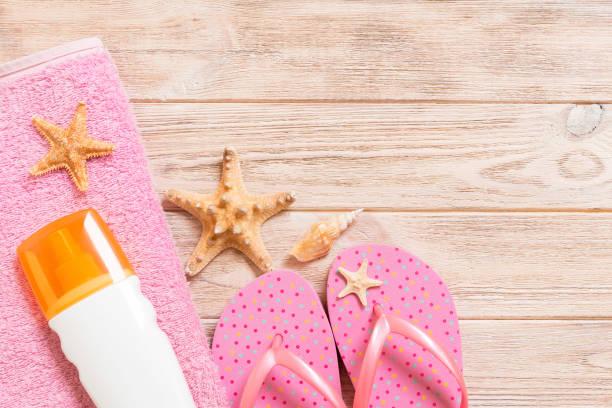 top uitzicht op beach flat lay accessoires. zonnebrandcrèmefles met zeeschelpen, zeesterren, handdoek en flip-flop op houten raadsachtergrond met exemplaarruimte - pink and orange seashell background stockfoto's en -beelden