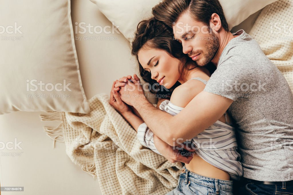 Top view of beautiful happy young couple hugging while sleeping on bed stock photo
