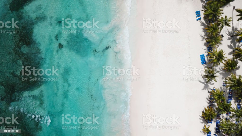 Top view of beautiful white sand beach with turquoise sea water and palm trees, aerial drone shot. Nature background stock photo