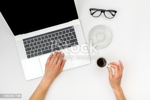 Top view of beautiful woman 's hands using laptop placed on white desktop. Flat lay