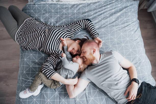 Blick auf schöne junge Mutter, Vater und ihre Tochter mit Blick auf Kamera und Lächeln, während auf dem Bett Kopf an Kopf – Foto