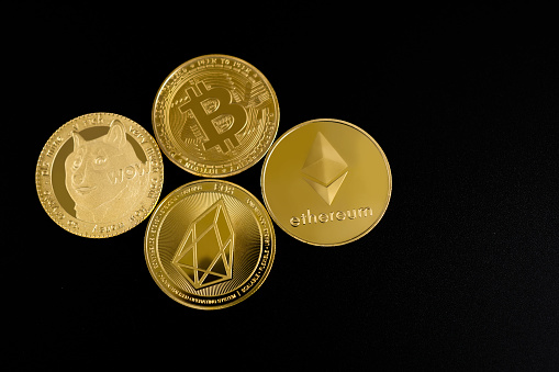 Top view of Bitcoin, Ethereum, EOS and Dogecoin coins on a black background.